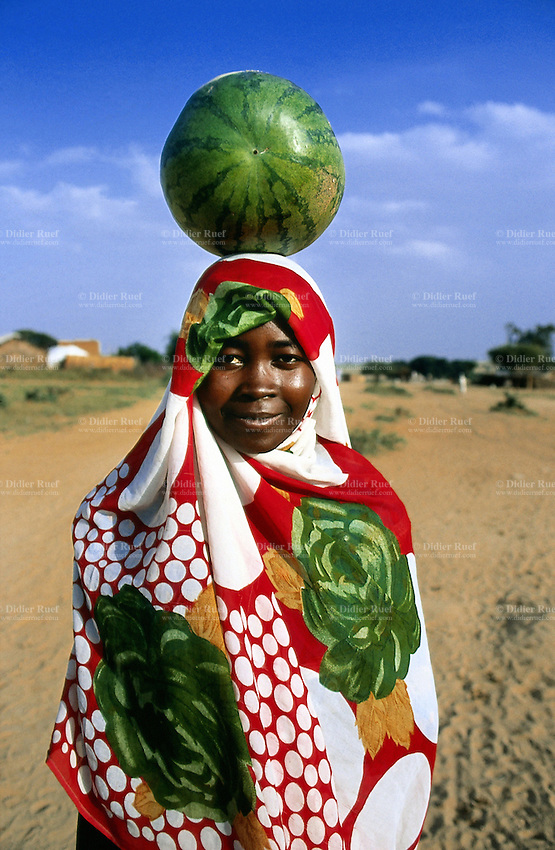 Sudan. West Darfur. Kerenek. A young woman wears a colorful veil which covers her head. She  carries a watermelon on her head. © 2004 Didier Ruef