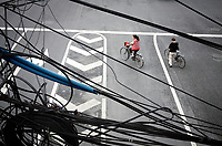 CHINA. Beijing. In the cenytre of the capital, electricity wires are strung together above the heads of passing cyclists. 2009