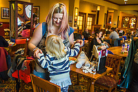 A mother breastfeeds her two year old daughter in the family restaurant and play area of a pub. The mother is standing and the boy is feeding while standing on a chair.<br /> <br /> Lancashire, England, UK<br /> <br /> Date Taken:<br /> 07-01-2015<br /> <br /> © Paul Carter / wdiip.co.uk