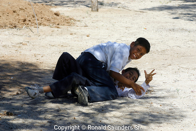 TWO SCHOOL KIDS HAVE FUN WRESTLING on the GROUND WHILE WATCHING PHOTOGRAPHER TAKE a PHOTO.