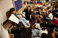 STUDENTS LISTENING TO FELLOW CLASSMATE GIVING PRESENTATION, TEACHER AND STUDENTS HAVE HANDS RAISED. ELEMENTARY SCHOOL STUDENTS. OAKLAND CALIFORNIA USA CARL MUNCK ELEMENTARY SCHOOL.