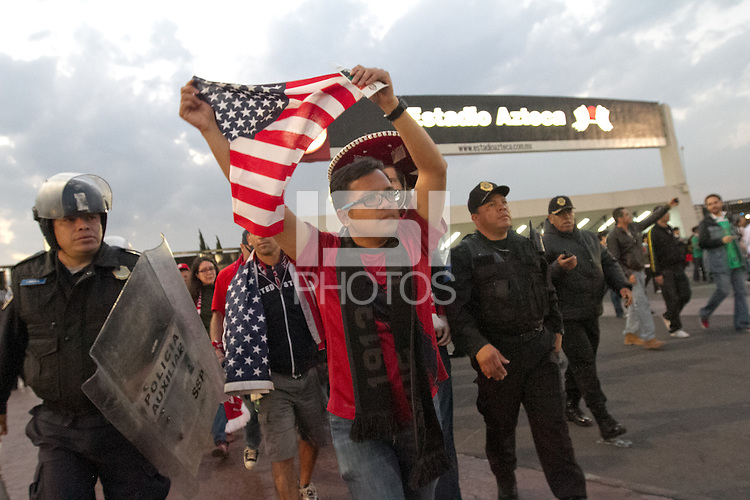 USA fans are heckled by Mexican fans as they walk into Azteca stadium escorted by Mexican police officers in riot gear for the USA vs. Mexico World Cup Qualifier in Mexico City, Mexico on March 26, 2013.