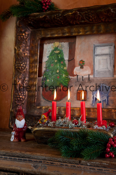 Detail of a Christmas still-life with red candles infront of a festive painting