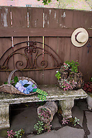Garden bench, harvested basket of hydrangeas, pot containers, antiques, recycled ornaments, charming, old garden tools, fence, cement