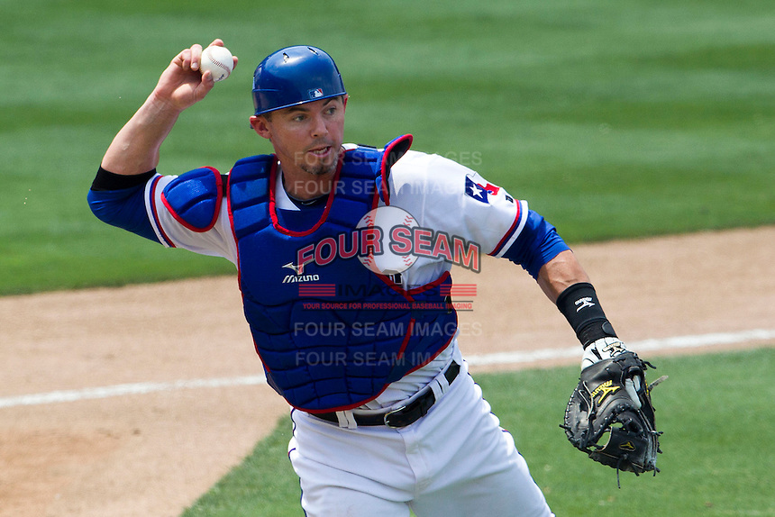 Round Rock Express catcher Eli Whiteside (18) makes a throw to first base against the Colorado Springs Sky Sox in the Pacific Coast League baseball game on May 19, 2013 at the Dell Diamond in Round Rock, Texas. Colorado Springs defeated Round Rock 3-1 in 10 innings. (Andrew Woolley/Four Seam Images).