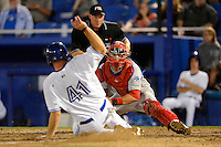 Clearwater Threshers catcher Logan Moore #5 tags out  first baseman Kevin Patterson #41 as umpire James Rackley gets in position to make the call during a game against the Dunedin Blue Jays at Florida Auto Exchange Stadium on April 4, 2013 in Dunedin, Florida.  Dunedin defeated Clearwater 4-2.  (Mike Janes/Four Seam Images)