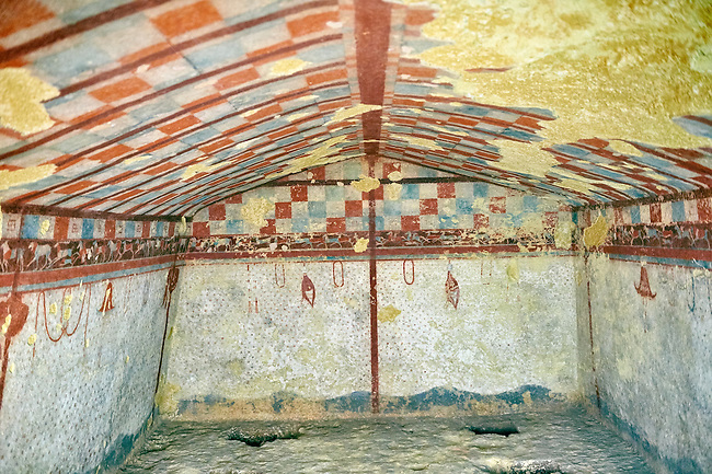 """Underground Etruscan tomb Known as """"Tomba del Cacciatore A single chamber with double sloping ceiling decorated with a painted chequered design, the rest of the tomb is decorated like a hunting tent with hanging wild ducks and hats. 510-500 BC. Excavated 1962, Etruscan Necropolis of Monterozzi, Monte del Calvario, Tarquinia, Italy. A UNESCO World Heritage Site."""