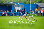 Knocknagoshel's James Walsh on a solo run as Lispoles Cathal O'Sé gives chase, in the County Football league division 4 relegation game.