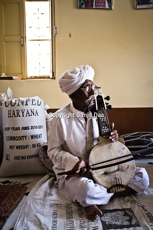 75-year-old Manganiyar artist and a Padmashree awardee, Saqar Khan plays his Kamancha (music instrument) during field recordings inside his house in Hamira village of Jaiselmer district in Rajasthan, India. Photo: Sanjit Das/Panos