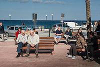 Malta, Bugibba, Northern region of Malta.<br /> <br /> In the winter a quiet tourist area with mainly older overwintering English tourists.  Many places are closed and lots of appartments are boarded up.<br /> Tourists here enjoying a sunny winter morning at the sea shore.<br /> <br /> Photo Kees Metselaar