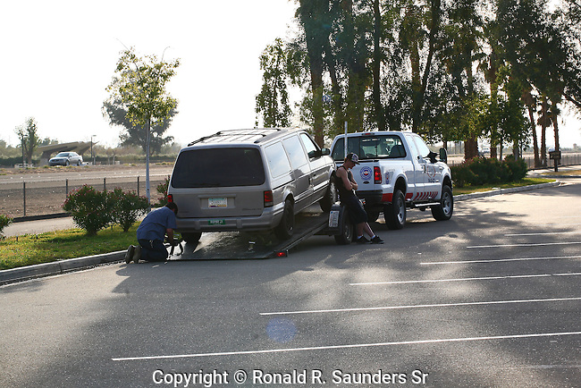 TOW TRUCK PREPARES TO TRANSPORT VEHICLE WHILE DRIVER LOOKS ON (3)