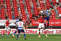 Michael Morrison of Reading out jumps Charlton's Macauley Bonne as Charlton's pop up fans look on from behind the goal during Charlton Athletic vs Reading, Sky Bet EFL Championship Football at The Valley on 11th July 2020