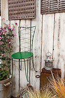Iron molds, hanging metal chair, lantern, clematis in pot, ornamental grasses, rustic barn wall, weathered implements
