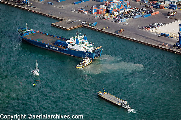 aerial photograph Seabord Trader freight ship pushed by tugboat Port of Miami Florida
