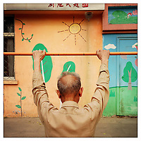 An elderly man taking exercise in a park in central Beijing.