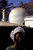The Gambia. Woman with white headscarf outside a mosque with minaret and crescent moon and star on the domed roof.