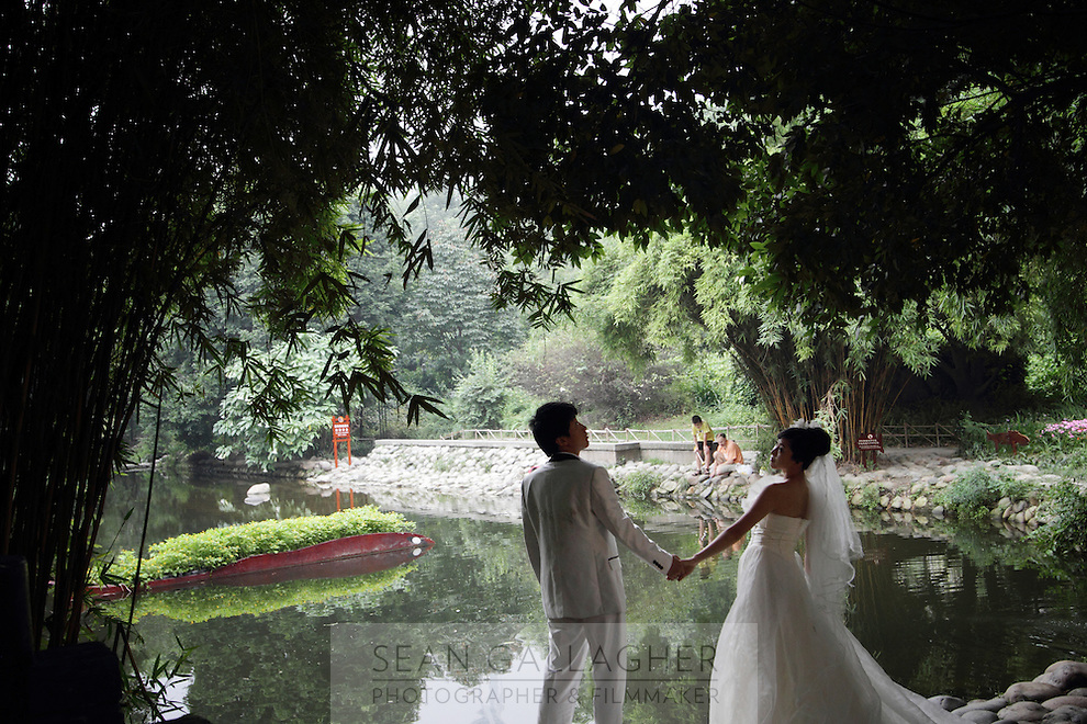 """A newlywed couple pose for photographs in the """"Living Water Garden"""" in Chengdu, Sichuan Province. The garden is a park aimed at highlighting the importance of the relationship between man and water. 2010"""