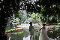 "A newlywed couple pose for photographs in the ""Living Water Garden"" in Chengdu, Sichuan Province. The garden is a park aimed at highlighting the importance of the relationship between man and water. 2010"