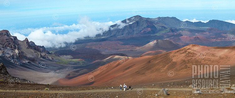 A family hiking the Sliding Sands Trail at Maui's Haleakala National Park stops to admire the view.
