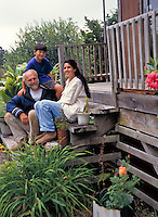 A family sits together on the wooden steps of their porch.