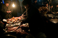 Street vendors prepare balyk, a type of fried fish, in a night market in the center of the Old Town section of Kashgar, Xinjiang, China.