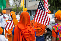 Muslim women waving American Flags, Kent Cornucopia Days, Kent, Washington State, WA, USA.