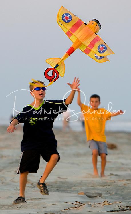 Boys watch as their kite takes flight at sunset.