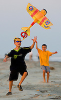 Boys watch as their kite takes flight at sunset.