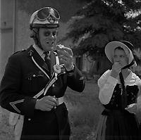 2 Juillet 1963. Vue d'un motard de la 5e Légion de Gendarmerie Départementale qui déguste une pêche avec une jeune fille portant un costume régional.