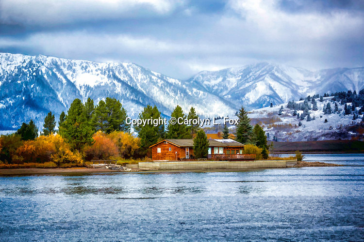 A cabin sits by a lake in front of snow covered mountains.