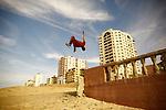 A Palestinian child plays gymnastics next to the Gaza port january 16 , 2017. Photo by Osama Baba