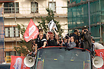 Alan Tate holds the trophy with Swansea City Football Club players and staff celebrating their promotion to the Premier League with an opentop bus tour of the city, where thousands of supporters turned out to show their appreciation..