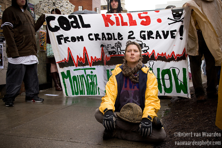 Amber Bockman sits in front of a banner in solidarity while protesters being led away by the police during and action against the Tennessee Valley Authority in Knoxville.TVA March in March, Mountain Justice Spring Break, March 14, 2009 (©Robert vanWaarden ALL RIGHTS RESERVED)