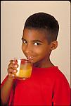 smiling young boy drinks orange juice