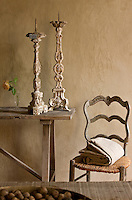 A pair of carved church candlesticks is displayed on a rustic sidetable beside a rare Louis XV provencale chair with a rush seat in the kitchen