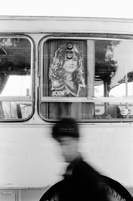 Iraq. Najaf. A young man walks by a sticker of an attractive young woman's face on a public bus. 26.02.04 © 2004 Didier Ruef .