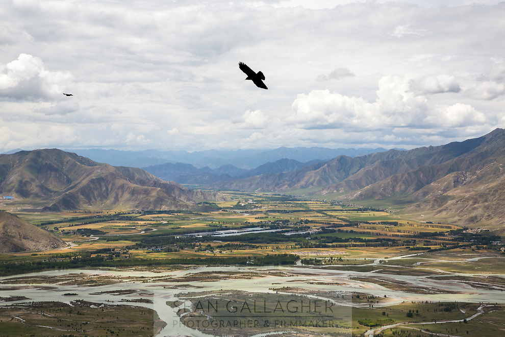 A bird flies over spectacular valleys near the Ganden Monastery in Tibet. Pilgrims circle the monastery which sits upon a mountain near Lhasa, offering spectacular 180 degree views of the surrounding countryside.