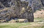 Old farm buildings under huge rock at Drangshlio