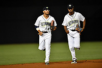 Center fielder Desmond Lindsay (2) and right fielder Jose Medina (8) of the Columbia Fireflies run in from the outfield during a game against the Lexington Legends on Saturday, April 22, 2017, at Spirit Communications Park in Columbia, South Carolina. Lexington won, 4-0. (Tom Priddy/Four Seam Images)