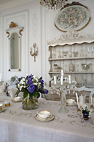 A carved wooden dresser displays a collection of glassware against one wall of the dining area