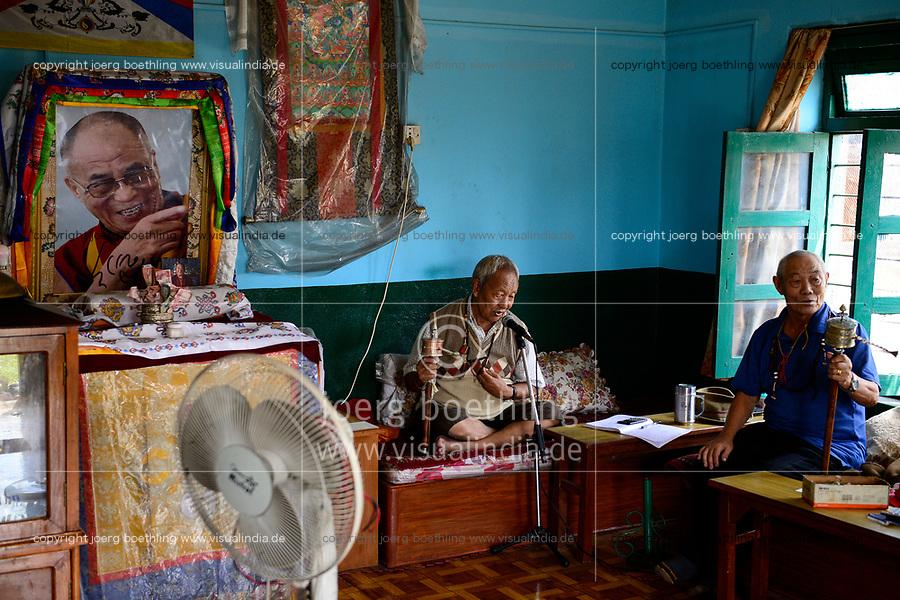 NEPAL Pokhara, tibetan refugee camp Prithvi, old tibetan freedom fighter during prayer time, image of HHDL Dalai Lama / tibetisches Fluechtlingslager Prithivi, alte Tibeter bei einem Gebet mit Gebetsmuehlen, Bildnis des Dalai Lama