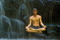 Man sits relaxing in waterfall while meditating