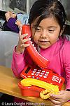 Preschool children ages 2-4 girl pretend play talking on telephone vertical