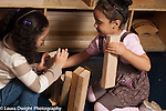 Preschool 3-4 year olds two girls working together building with blocks