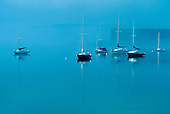 Sailboats at anchor in Marquette, Michigan's lower harbor. Lake Superior. Soo Line ore dock in the background fog.