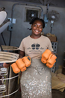 Haiti, Port-au-Prince. Artisan business, Papillon. Produce ceramics, jewelry, t-shirts. Over 300 women on payroll (men work her as well), making about $15 a day. This woman and her family were deeply affected by the earthquake and she has worked heres since then, for seven years. Taking ceramic  mugs from the kiln. MR