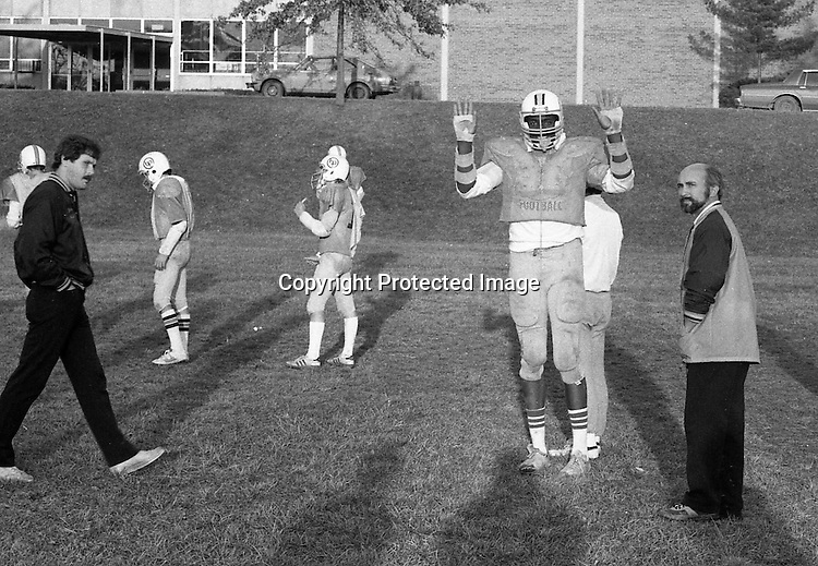 Bethel Park PA:  View of future college & NBA basketball star Armen Gilliam horsing around at practice. Coaches Don Porter (left) and Chuck Boig (right). Armen played defensive end, other notable players included; Shawn Morton QB, Steve Berlin (T), Eric Coss (T), Van Richardson (LB), Evan Evanovich (TE).<br /> The team made a great run in the WPIAL AAAA playoffs beating the #2 rated high school football team in the nation, North Hills in 3 overtimes, and then top 5 Gateway the next week.  Came up a little short against Mt Lebanon in the championship game at Pitt Stadium.<br /> Coaches included Head Coach & OC Bob King, Don Porter (DC), Dave George (LB, TE), Leo Henne (DL), Dave Luptak (R, DB), Gerard Runco (R, Secondary), Chuck Boig (QB, DB) and Mike Stewart (RB, DB).<br /> RECORD 9-4 WPIAL AAAA Runners Up.<br /> L 34-14 against Thomas Jefferson<br /> W 26-0 over Trinity<br /> W 17-6 over Ringgold<br /> W 21-14 over North Allegheny<br /> W 13-7 over Cannon McMillian<br /> L 17-0 against Mt Lebanon<br /> W 19-14 over Baldwin<br /> L 10-6 against Keystone Oaks<br /> W 13-0 over Chartiers Valley<br /> W 31-14 over Upper St Clair<br /> PLAYOFFS<br /> W 33-27 over North Hills (3 overtimes)<br /> W 20-14 over Gateway<br /> L 30-14 against MT Lebanon
