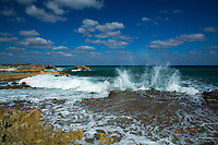 Beautiful, turquoise Caribbean Sea waves crashing on shore, under a blue sky with white clouds, in Laguna Columbia, south of Cozumel Island, Mexico