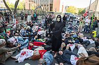 """Protest gegen die Jahreshauptversammlung des Ruestungskonzern Rheinmetall am Dienstag den 8. Mai 2018 in Berlin.<br /> Verschiedene Friedensgruppen und die Linkspartei haben zu dem Protest aufgerufen.<br /> Im Bild: Die Kundgebungsteilnehmer haben sich zu einem """"Die in"""" auf die Strasse gelegt, waehrend ein als Tod verkleiderter Teilnehmer zwischen den """"Toten"""" steht.<br /> 8.5.2018, Berlin<br /> Copyright: Christian-Ditsch.de<br /> [Inhaltsveraendernde Manipulation des Fotos nur nach ausdruecklicher Genehmigung des Fotografen. Vereinbarungen ueber Abtretung von Persoenlichkeitsrechten/Model Release der abgebildeten Person/Personen liegen nicht vor. NO MODEL RELEASE! Nur fuer Redaktionelle Zwecke. Don't publish without copyright Christian-Ditsch.de, Veroeffentlichung nur mit Fotografennennung, sowie gegen Honorar, MwSt. und Beleg. Konto: I N G - D i B a, IBAN DE58500105175400192269, BIC INGDDEFFXXX, Kontakt: post@christian-ditsch.de<br /> Bei der Bearbeitung der Dateiinformationen darf die Urheberkennzeichnung in den EXIF- und  IPTC-Daten nicht entfernt werden, diese sind in digitalen Medien nach §95c UrhG rechtlich geschuetzt. Der Urhebervermerk wird gemaess §13 UrhG verlangt.]"""