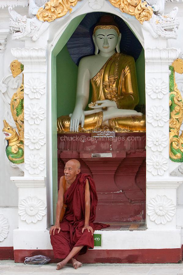 Myanmar, Burma.  Shwedagon Pagoda, Yangon, Rangoon.  Buddhist Monk.  Behind him a Buddha Statue demonstrates the mudras (hand gestures) of earth-touching (bhumisparsha) and wisdom (dhyana).
